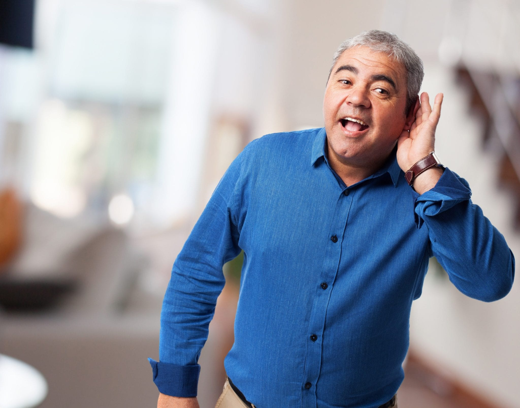 Man holding his ear listening out | Clarity Hearing