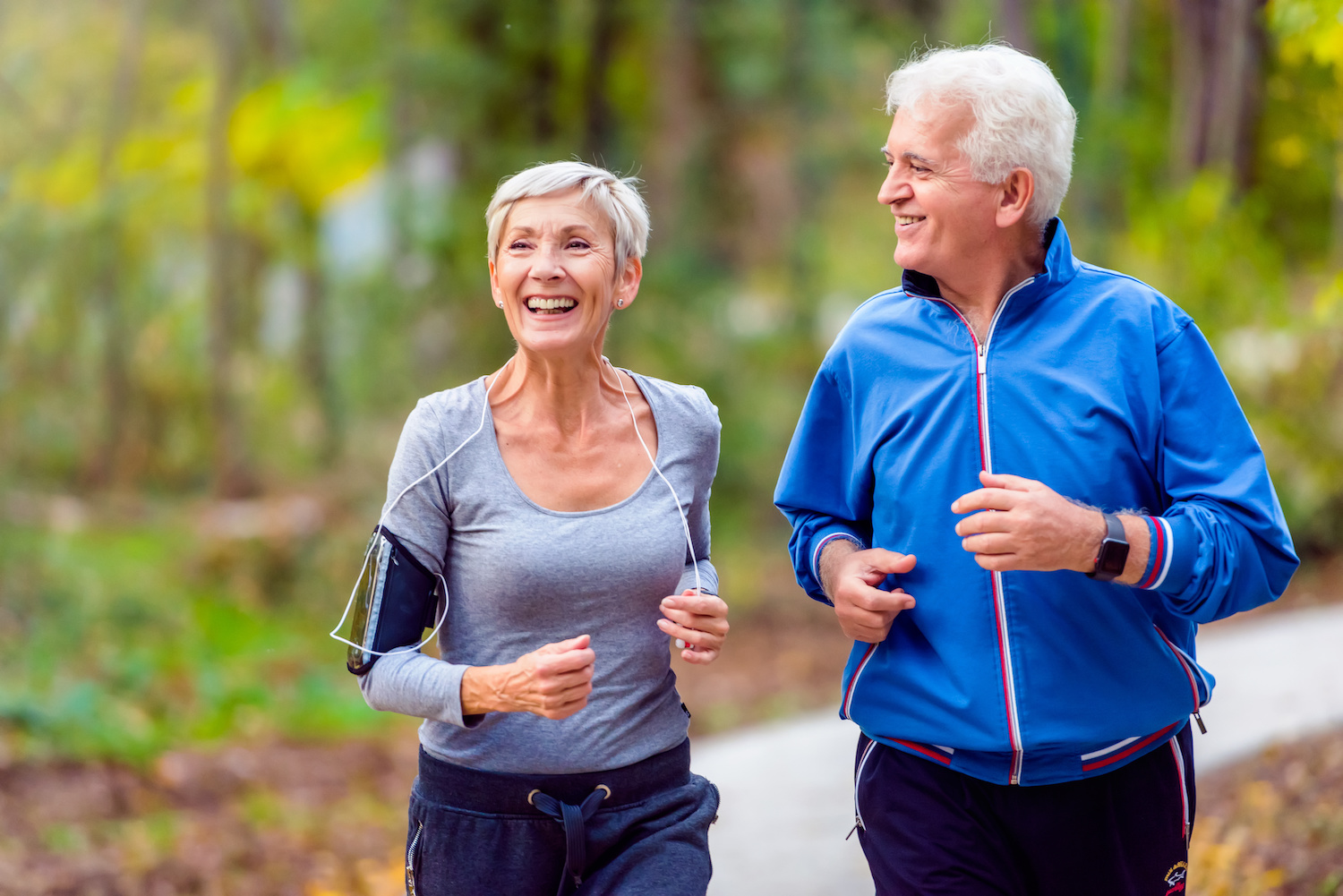 Smiling senior active couple jogging together in the park   Clarity Hearing