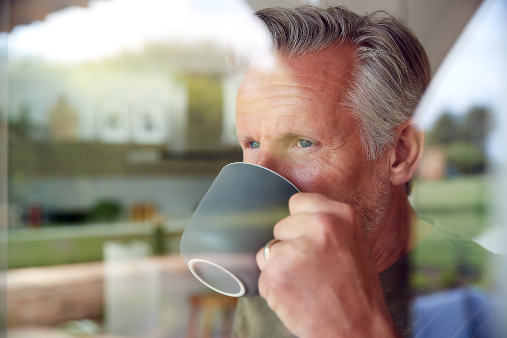 Senior Man Standing And Looking Out Of Kitchen Door Drinking Coffee Viewed Through Window   Clarity Hearing